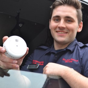 Firefighter holding a smoke alarm