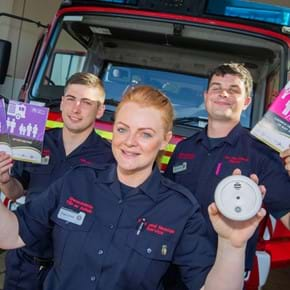 Apprentices holding smoke alarms and leaflets