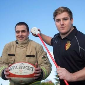 Firefighter and rugby player with a smoke alarm